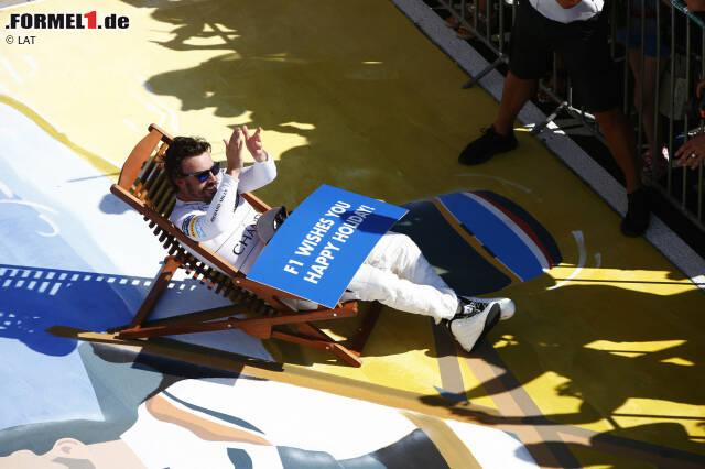 """#PlacesAlonsoWouldRatherBe macht weiter die Runde. Diesmal im Zuge einer PR-Aktion des Hungarorings, mit dem die Formel 1 in die Sommerpause verabschiedet wird. Für Martin Brundle eine """"Verschwendung von Talent"""", dass Alonso nicht auf, sondern unter dem Podium ist. Jenson Button kontert: Ein bisschen Spaß muss sein!"""