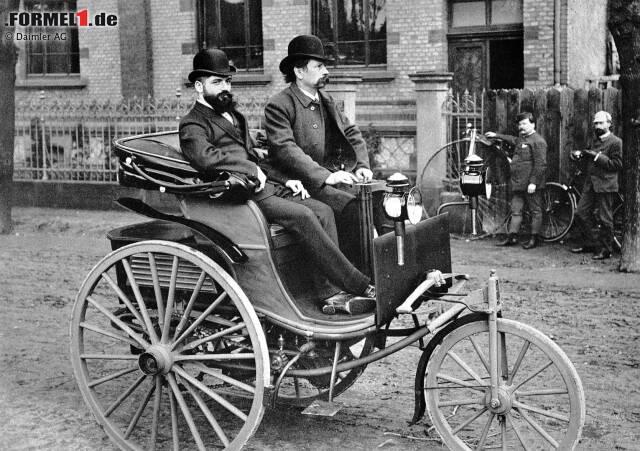 Der Patent-Motorwagen im Jahre 1887, eine Weiterentwicklung des ersten Motorwagens von 1886. Am Steuer Carl Benz, neben ihm sein kaufmännischer Mitarbeiter Josef Brecht.