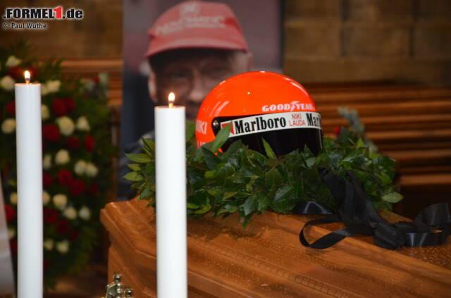 Österreich nimmt Abschied von Niki Lauda: Auf dem geschlossenen Sarg liegen ein Lorbeerkranz und ein Rennhelm. Der Leichnam trägt einen Rennoverall. Ein letztes Mal.